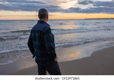 An elderly man stands alone on the Mediterranean beach and looks thoughtfully at the water. The sun has just set and the sky is orange in color.