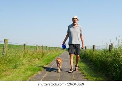 Elderly man with straw hat walking the dog in summer season