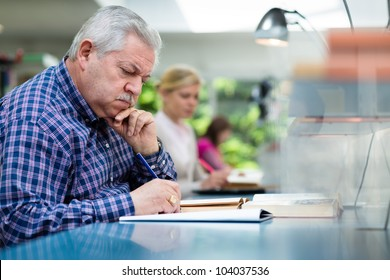Elderly man studying with a group of young college students in library and taking notes