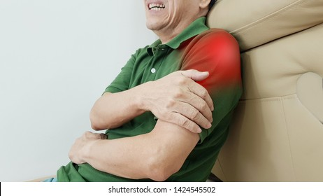 Elderly man suffering from shoulder pain with painful facial expression. Shoulder pain may cause from muscle strain, tendinitis, ligament sprain, fracture or arthritis disorder. Medical symptom