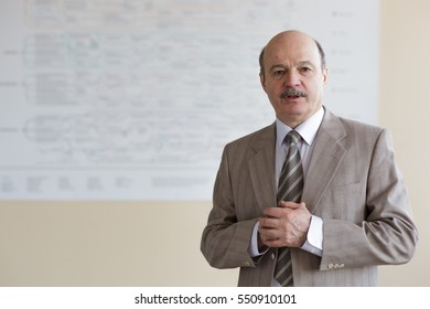 An elderly man in a suit reports on scientific work or lecturing to students. Public speaking at a conference or meeting.