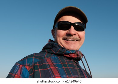 An elderly man in sunglasses and a baseball cap looks down and smiles