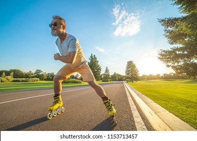 The elderly man in sunglasses rollerblading on the road on the sunset background