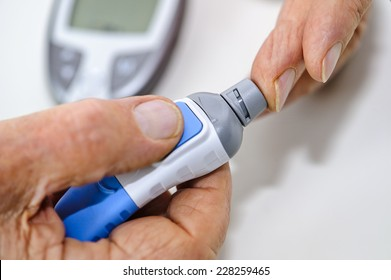 An elderly man takes a drop of blood to measure his blood sugar level at home. The picture depicts drawing a drop of blood. The blood sugar measuring device is visible in the background