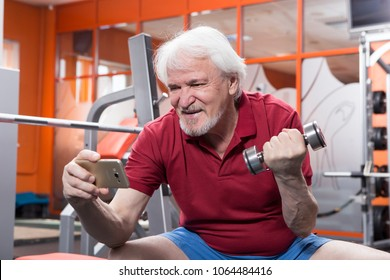 Elderly man taking a selfie with smartphone in fitness center