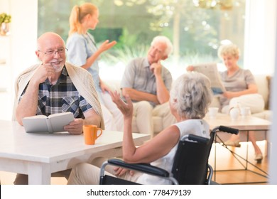 Elderly man talking with disabled woman while sitting together at table in common room