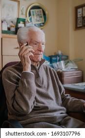 Elderly man talking on phone sitting at home