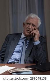 Elderly man is talking on the phone