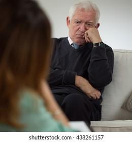 Elderly man talking with psychotherapist