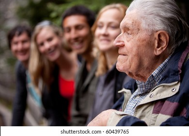 An elderly man telling stories to a group of young people in the forest
