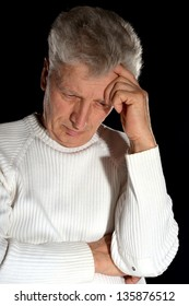 elderly man thinking about problems on a black background
