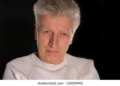 An elderly man thinking about something on a black background