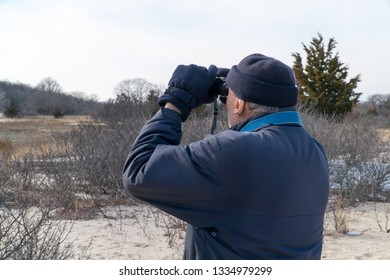 Elderly man using binoculars to bird watch in the park during the winter time. Wearing jacket hat and gloves searching for flying wildlife.