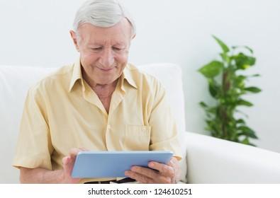 Elderly man using a digital tablet on a sofa