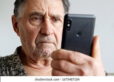 Elderly man using smartphone, mobile phone in male hands close up. Concept of online communication in retirement, sms, social media, bad news