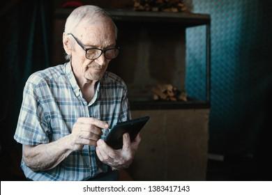Elderly man using tablet at home