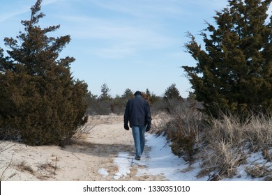 Elderly man walking alone through trail in the woods past tree gap on a cold winter day after snow fall on path. Day time exterior