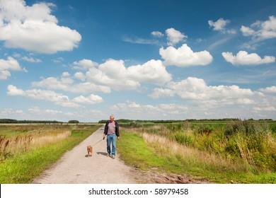 elderly man is walking the dog in nature landscape