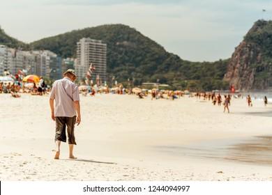 Elderly man walking head down on Copacabana beach in Rio de Janeiro, Brazil