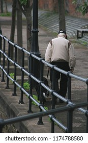 Elderly man walking his dog with head bowed.