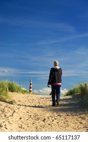 Elderly man is walking with his dog in the dunes with lighthouse