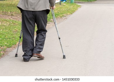 an elderly man walking on crutches on the street