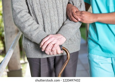 Elderly man with walking stick moving with nurse, detail on the hands.