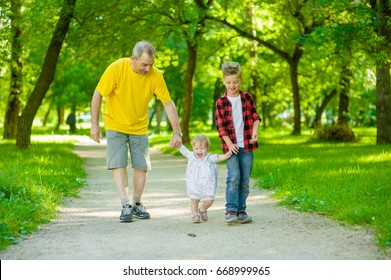 An elderly man walks with his grandchildren