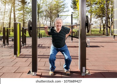Elderly man warming up at the weights bar in the fitness park (outdoors gym)