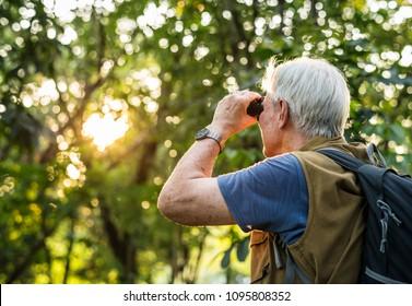 Elderly man watching birds with binoculars