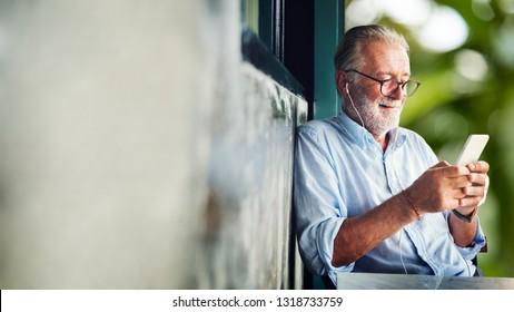 Elderly man watching online movie from his phone