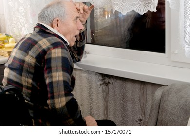 Elderly man watching through a window at night reacting with a look of horror to something that is happening in the darkness