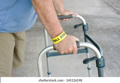 An elderly man wearing a fall risk bracelet around his wrist using a walker