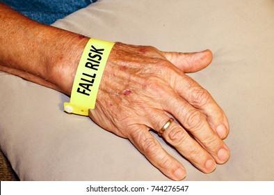 Elderly man wearing fall risk bracelet on his wrist on top of a pillow