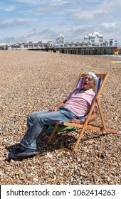 Elderly man wearing a knotted hankerchief on his head relaxing on the beach. Southsea, England UK 2017