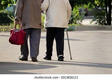Elderly man and woman with cane walking down the street, rear view. Old couple holding hands together, concept of old age, diseases of the joints and spine - Shutterstock ID 2013836111