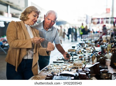 Elderly man and woman consider things in flea market. High quality photo
