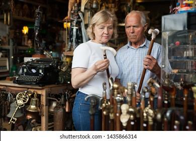 Elderly man and woman examine rare walking stick on flea market