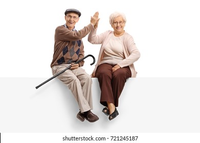 Elderly man and woman seated on a panel high-fiving each other and looking at the camera isolated on white background