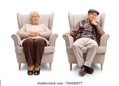 Elderly man and an elderly woman sitting in armchairs and looking at the camera isolated on white background