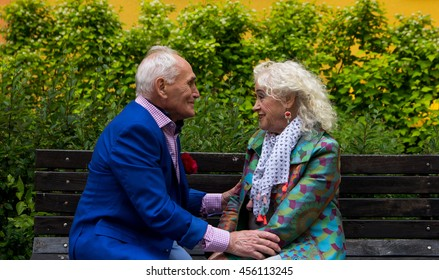Elderly man and an elderly woman sitting on a bench talking. A man holds a woman's hands.