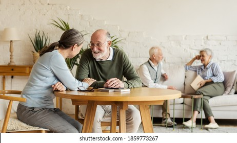 Elderly man and woman sitting at table and enjoying joyful talk, another senior couple communicating in background sitting on sofa in common room of assisted living home