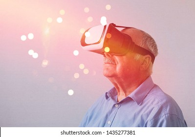 Elderly man in wonderment at a Virtual Reality experience wearing a headset with a glowing bokeh of magical lights in front of him