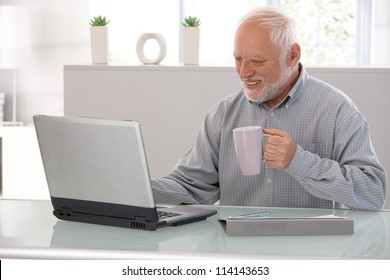Elderly man working on laptop, smiling, looking at screen, drinking tea.