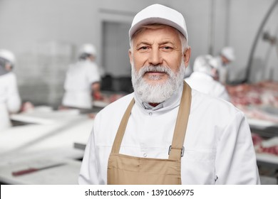 Elderly man working on sausage production, factory. Professional in white uniform, white cap and brown apron standing, posing and looking at camera. Meat manufacturing.