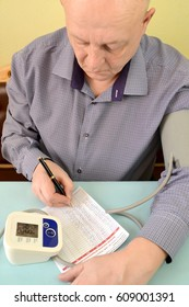 The elderly man writes down indicators in the diary of control of arterial pressure