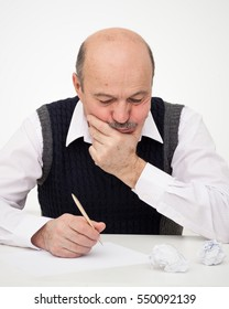 Elderly man writes, draws something on a piece of paper, to fill in an application or a will. Think of the solution to the problem or a difficult task
