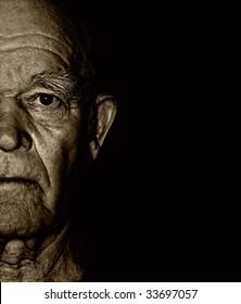 Elderly man's face over black background
