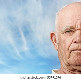 Elderly man's face over blue sky