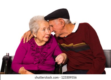 Elderly married couple with an affectionate pose on a white background.